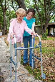 caregiver assisting elderly to walk