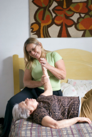 caregiver exercising an elderly
